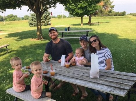 Family enjoying their donuts and cider at the picnic table